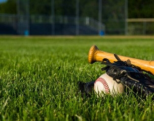 a baseball, glove and bat on a baseball diamond.