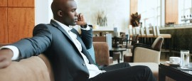 Young businessman sitting relaxed on sofa at hotel lobby making a phone call waiting for someone.