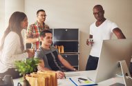 Diverse group of multi-ethnic young adult business people assembled around desk looking at something on their computer monitor