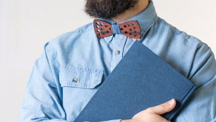 Bearded man with a wooden bow tie holding a blue notebook