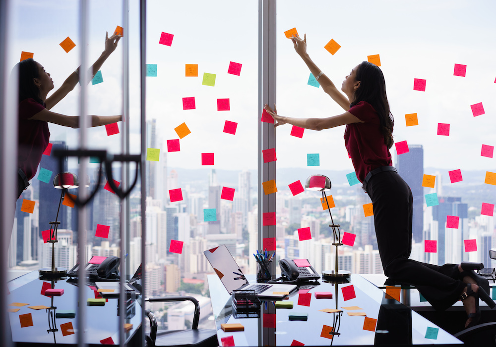 Mixed race secretary working in modern office in skyscraper, sticking adhesive notes with tasks on window. The girl feels stressed and overwhelmed