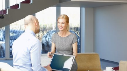 Senior businessman interviewing business woman while sitting at office.