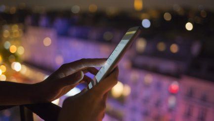 Woman using her mobile phone , city skyline night light  background