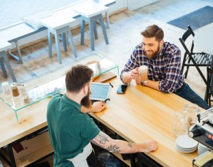 Cheeful attractive young man drinking coffee in cafeteria and talking to barista