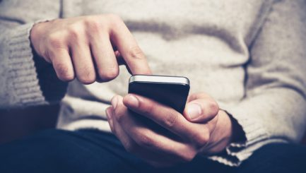 Closeup on a man's hands as he is sitting on a sofa and using a smartphone